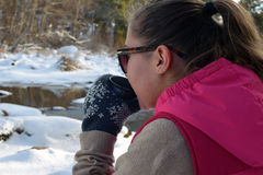 Young woman drinking hot tea on winter forest. And watching frozen river Stock Image