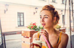 Young Woman Drinking Ice Coffee in a Cafe Royalty Free Stock Photography