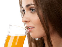 Young woman drinking juice, on the white background Royalty Free Stock Photo
