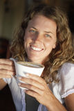 Young woman drinking latte in cafe, smiling, close-up, portrait Royalty Free Stock Image