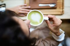 Young woman drinking Matcha green tea latte in the coffee shop. Close-up of young woman drinking Matcha green tea latte on wodden table in the coffee shop. Top royalty free stock images