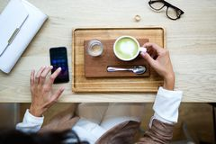 Young woman drinking Matcha green tea latte in the coffee shop. Close-up of young woman drinking Matcha green tea latte on wodden table in the coffee shop. Top royalty free stock photo