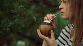 Young woman drinking mate outdoor stock video