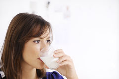 Young woman drinking milk. On the white background Royalty Free Stock Image