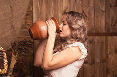 Young woman drinking milk. On a background of the rural interior Stock Photography