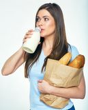 Young woman drinking milk and holding bag with bread. Isolated portrait Stock Photos