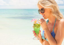 Young woman drinking mojito cocktail on the beach Royalty Free Stock Photos