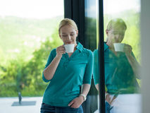 Young woman drinking morning coffee by the window Royalty Free Stock Image