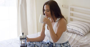 Young woman drinking a mug of fresh coffee Stock Images