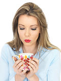 Young Woman Drinking a Mug of Tea or Coffee Royalty Free Stock Images
