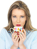 Young Woman Drinking a Mug of Tea or Coffee Stock Image
