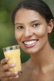 Young Woman Drinking Orange Juice. Closeup of young woman drinking orange juice in outdoor setting. Vertically framed shot Royalty Free Stock Image