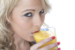 Young Woman Drinking Orange Juice Stock Images