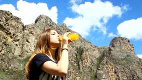 Young woman drinking orange juice from a bottle stock footage