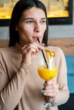 Young woman drinking orange juice in cafe. Pretty young woman drinking orange juice in cafe Royalty Free Stock Photography