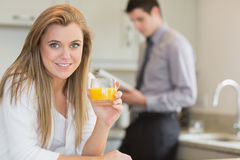Young woman drinking orange juice in kitchen Royalty Free Stock Photography
