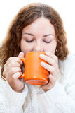 Young woman drinking from orange mug Stock Images