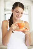 Young Woman Drinking Out Of An Orange Cup Royalty Free Stock Photos