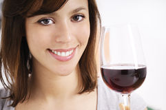 Young woman drinking red wine. On white background, smiling and looking in camera Royalty Free Stock Photo