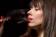Young woman drinking red wine from a glass Stock Photography