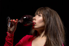 Young woman drinking red wine from a glass Stock Images