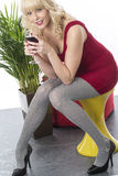 Young Woman Drinking Red Wine Red Dress Grey Tights High Heels. Attractive Young Woman Drinking Red Wine Red Dress Grey Tights High Heels Stock Image