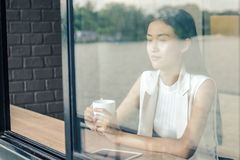 Young woman drinking relaxing coffee. In coffee shop Stock Images