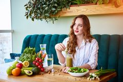 Free Young Woman Drinking Smoothie In The Beautiful Interior With Green Flowers On The Background And Fresh Fruits And Vegetables. Royalty Free Stock Images - 154445669