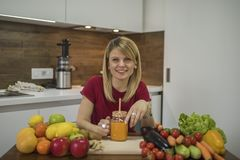 Young woman drinking smoothie in the kitchen royalty free stock photos