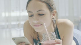 Young woman is drinking a smoothies and using a fitness app on her smartphone.