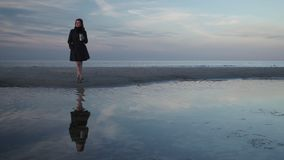 Young woman drinking take away coffee outdoors on a beach during a cold blue sunset with clear reflection in water on. The Baltic Sea in Latvia stock video