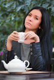 Young fashion woman drinking tea at sidewalk cafe Stock Photo