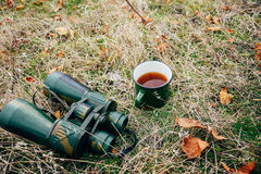 Young woman drinking tea on a autumn nature. Binocular, traveler Stock Images