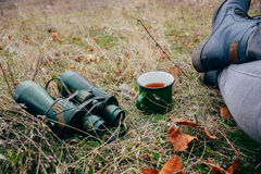Young woman drinking tea on a autumn nature. Binocular, traveler Royalty Free Stock Images