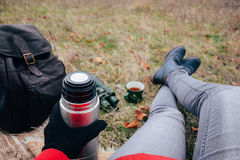 Young woman drinking tea on a autumn nature. Binocular, traveler Royalty Free Stock Photo