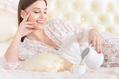 Young woman drinking tea in bed Stock Images