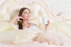 Young woman drinking tea in bed Royalty Free Stock Photos