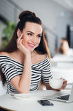 Young woman with drinking tea in a cafe. Beautiful adult woman with a cup of cappuccino at a cafe. Smiling brunette with Royalty Free Stock Photography