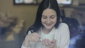 Young woman drinking tea in a cafe stock video footage