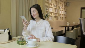 Young woman drinking tea in a cafe stock footage