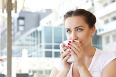 Young woman drinking tea in a cafe outdoors Royalty Free Stock Photo