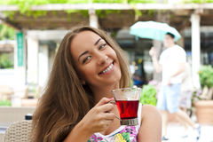Young woman drinking tea in a cafe outdoors Stock Images