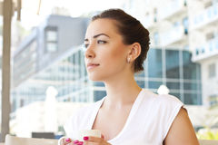 Young woman drinking tea in a cafe outdoors Stock Photography