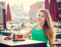 Young Woman Drinking Tea in a Cafe Outdoors. Stock Images