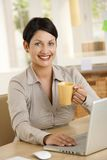 Young woman drinking tea at desk Stock Image