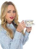 Young Woman Drinking Tea. A DSLR royalty free image, of an attractive young woman, with blonde hair, holding a cup and saucer, looking happy and relaxed. Against Stock Photography