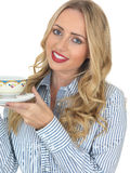 Young Woman Drinking Tea. A DSLR royalty free image, of an attractive young woman, with blonde hair, holding a cup and saucer, looking happy and relaxed. Against Royalty Free Stock Photo
