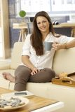 Young woman drinking tea at home. On sofa, smiling, looking at camera Stock Photo