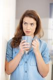 Young woman drinking tea at home standing Stock Photography