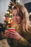 Young woman drinking tea near Christmas tree at home. With Christmas lights on the background Royalty Free Stock Images
